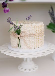 Cream ruffled wedding cake with lavender details