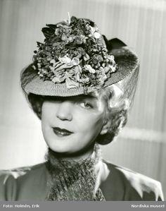 Från Legroux Soeurs. Porträtt av kvinna i hatt med garnityr på kullen och band av tyll. Foto: Erik Holmén, 1942.