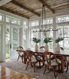 Tall windows and exposed wood beam ceiling. Wooden dining table and chairs.