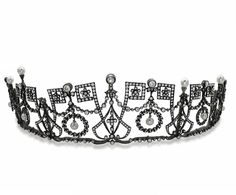 A diamond and natural pearl belle epoque tiara, 1905, possibly French. Designed as a series of diamond wreath-like and some decidedly art deco box-like shapes. With five angular motifs, linked with garlands to diamond and natural pearl spacers. A tiara on the cusp of the belle epoque and art deco. Sold by Christie's, Paris for an undisclosed sum 2013.