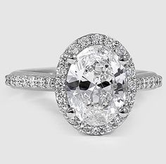 An intricate halo of diamonds embraces and accentuates the center oval shaped diamond of this brilliant antique style ring.