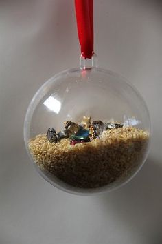 """""""I Spy"""" Nativity Ornament - use the clear bead filler instead.  (Tiny nativity figures originally came from Michael's.)  This would be cute for Easter too. - Use a mini cross, donkey, palm leaf - Kind of like the Ressurection Eggs but in 1 ornament or I spy bag."""