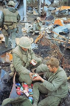 14 Feb 1968, Hue, South Vietnam --- Packs of cigarettes are distributed to U.S. Marines during pause in fighting on rubble-filled sight. --- Image by © Bettmann/CORBIS