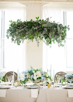 Dramatically draped with eucalyptus and camellia foliage, a leafy chandelier was the indisputable showpiece of the shoot. Suspended above the tabletop, it complemented rather than overwhelmed the centerpiece beneath it. | Photo by Deborah Zoe #WeddingFlowers