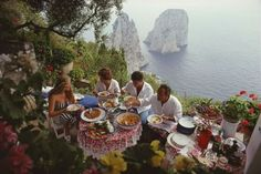 """Dining Al Fresco on Capri"", Slim Aarons Italian artist and actress Domiziana Giordano, Italian author Francesca Sanvitale, Dino Trappetti and Umberto Terrelli dining al fresco on a terrace overlooking the waters off the coast of the island of Capri, Italy, in August 1980."