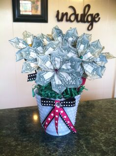 Dollar flowers for an 18 th birthday gift. Easy to make tutorials on Pinterest. Glue dot gems to each flower and add ribbon for leaves. Easy and cute. I found the container at my local church basement thrift store.