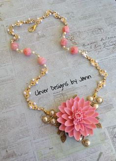 B'sue components used are a large pink flower that is attached to a necklace blank, leafs, filigree spiral components and flat back pearls .. beautiful gold plated chain links, rose beads and pearls complete this necklace .. Designed by Jann Tague .. Clever Designs https://www.facebook.com/JewelsByJann