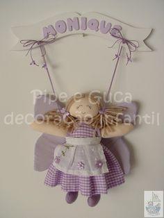 Enfeite maternidade fada (cód. MA 0098). Acompanha uma fada. Pode ser feita em outras cores e tecidos. Personalizamos com o nome do bebê.   ** As bonecas estão sujeitos à disponibilidade de estoque. Caso não tenhamos exatamente as bonecas apresentadas no produto, teremos opções para substituição.  Consulte-nos.  ** PRODUTO ARTESANAL SUJEITO À PEQUENAS VARIAÇÕES.  > Coordene toda a decoração e as lembrancinhas com a linha de produtos  PIPEeGUCA ENXOVAL, acesse e confira: www.pipeeguca.elo7.com...