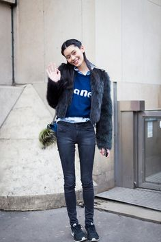 A button-up is worn under a graphic sweater and fur coat with black skinny jeans, a crossbody bag and black tennis shoes.