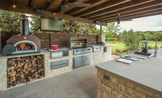 This breezy kitchen seriously has it all: a wood burning pizza oven, grill, side burner, egg smoker, sink, refrigerator, trash chute, serving station, and plenty of storage. Credit: AguaTerra Outdoors