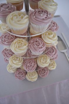 White choc mud and strawberry cheesecake cupcakes with piped buttercream rose swirls and pearl cachous. Cutting cake: Choc mud with palette iced white choc buttercream, satin ribbon and cascading flowers. Topper provided by bride.