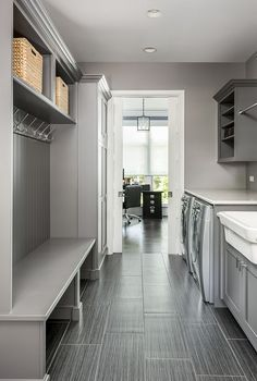 This grey mudroom/laundry room is so practical and the tile is really low-maintenance, which is a must in this space grey mudroom laundry room ideas garage entry Family Home with Grey Exterior and Interiors Mudroom Laundry Room, Laundry Room Layouts, Laundry Room Remodel, Laundry Decor, Small Laundry Rooms, Laundry Room Design, Laundry Room Inspiration, Küchen Design, Design Ideas