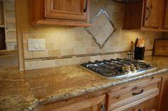 Custom designed kitchen with wood cabinets, tile backsplash, and granite countertops
