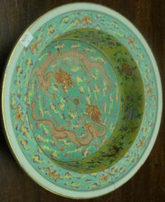 Lot 138 TURQUOISE: A Chinese Export porcelain basin, Qianlong, of circular straight sided form, with wide upturned rim enamelled in the famille palette with dragons on a turquoise ground, the sides with Buddhistic symbols on a yellow ground, 33cm diameter, (broken and re-stuck, elements missing).