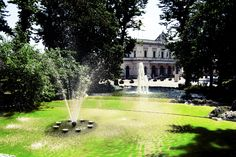 glimpse of monza railway station, surrounded by the fountain and the trees