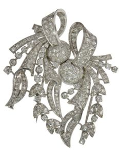 AN ART DECO DIAMOND PLATINUM AND GOLD DOUBLE CLIP BROOCH, CIRCA 1935. Mounted in platinum and white gold, with knotted ribbons and flower garlands set with pavé diamonds.