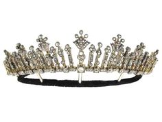 Antique diamond tiara/necklace, English, circa 1880 in gold and silver Articulated row of box collets set with cushion shaped old cut diamonds, each suspending a bar set with clusters of cushion shaped old cut diamonds in millegrain collet settings, seven with extended stylized foliate form pendants, all 100 diamonds with an approx total weight of 13.50 carats, in silver topped gold, with a cable chain for use as a necklace, with a silver frame for use as a tiara, in fitted leather necklace…