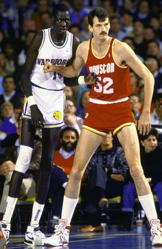 Manute Bol (7-7), the tallest player in NBA history, and Chuck Nevitt (7-5), the tallest NBA champion in history, post up during a Warriors-Rockets game on Jan. 20, 1989 in Oakland, Calif.