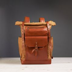 Yellow and orange waxed canvas leather backpack. Roll-top rucksack