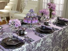 Cocktail Party : Sandra created a vision in lavender for this tablescape. Gunmetal plates, cups, saucers, print table runners and a silver tea set say bold but classy — while flowers and a three-tiered cake stand add a delicate touch.