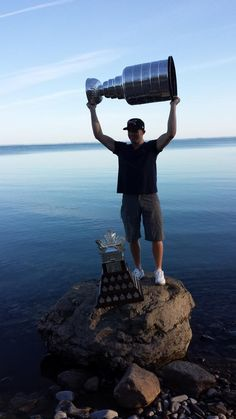 Patrick Kane hoists the Stanley Cup with Lake Erie in the background and the Conn Smyth Trophy on the rock in front of him 8/24/13