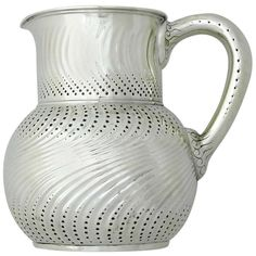 circa 1880 sterling silver pitcher by Tiffany & Company of New York, evocative of master designer Osborne's wave and beaded motifs. The pitcher has a bulbous body and applied handle. The chasing is superb. Dimensions 7 1/4 inches high. Weight 22 ozs. Marked