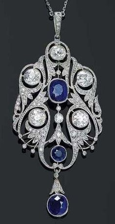 AN ART DECO SAPPHIRE & DIAMOND NECKLACE, ca. 1920. Very fancy openwork pendant in the shape of a stylized flower, set with 2 sapphires & 5 old-mine-cut diamonds, 110 old-mine-cut diamonds & diamond roses, suspending an articulated oval sapphire drop, mounted in platinum, with a chain set with 20 old-mine-cut diamonds.