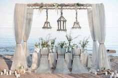 Add luxury to your beach dining space with this beautifully draped fabric and  matching chair dressing. #beachweddings #tabledecor #beachdining