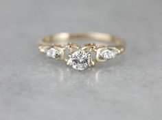 This piece has wonderful dimension! Tiny crescent moon shapes flank the center diamond in this beautiful ring. The diamond itself is set high, letting plenty of light in for maximum sparkle. Smaller diamonds are set along the shoulders creating a cascade of glitter. Metal: 14K Yellow and White Gold Gem: Diamond .20 Carats, VS1 in Clarity, J in Color Gem Measurements: 4.1 mm, Round Accents: 4 Diamonds totaling .10 Carats Ring Size: 6.75 Marks: ALB 14K Stamped on the inside band  SKU #…