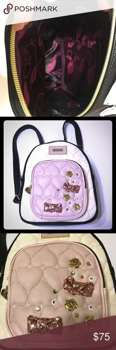 NWT Betsey Johnson Winged Heart Cream Backpack Get this NWT Betsey Johnson Winged Heart Peach, Cream and Black Backpack. Straps are adjustable. Has two pockets, one large front and a smaller front. Inside zipper pocket. Decorative pink sequin bows with gold roses. Too cute. Betsey Johnson Bags Backpacks