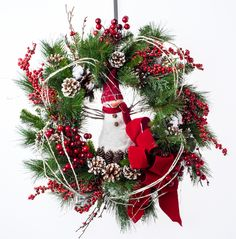Adorable glistening snowman set in a snowy evergreen wreath of berries and pine cones. Adorned with birch twigs and a red velvet bow. Perfect above a mantel or on a front door if protected from weather. $159