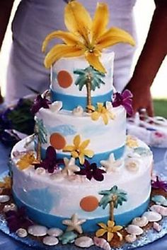Three tier Hawaii Maui theme wedding cake garnished with tropical pine trees and seashells. And a yellow lilly wedding cake topper. From www.mauiweddingcakes.com         ........   #wedding #cake #birthday