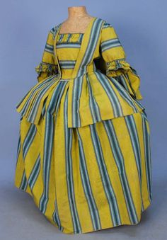 STRIPED SILK PET-EN-L'AIR and PETTICOAT, c. 1750. Lime green silk ottoman having wide ombree blue, black and white stripe, the sacque back jacket with double fan shaped cuff trimmed in looped cord, pleated petticoat with center back inverted pleat, open at both sides from waist bound in white linen tape with linen ties, hem bound in gold linen, unfinished stommacher trimmed with self furbelow, completely unlined.