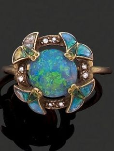 An Art Nouveau ring attributed to Eugene Feuillâtre, circa 1900. The ring featuring a round opal cabochon within a ring set with rose-cut diamonds and decorated with enamelled winged insects on four compass points. #Feuillatre #ArtNouveau #ring