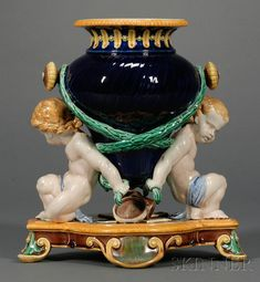 Wedgwood Majolica Trentham Vase, England, c. 1865, polychrome decorated and modeled with two putti supporting a central vase, agricultural implements scattered atop the raised base.