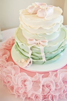 Ruffled baby shower cake with mint green ombre layers and a pretty pink bow