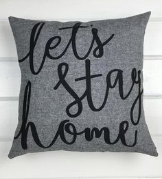 """Let this pillow make the decision for you and your favorite couch companion. The hand-lettered text is screenprinted on yarn-dyed linen and reads, """"Let's Stay Home"""". Add it to your collection of pillows on the sofa or bed for a snuggly accent for your stay-at-home party."""