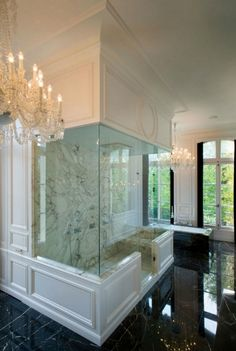 Black marble tiles floor, seamless glass shower with marble slab shower surround, black marble drop-in tub and crystal chandeliers.