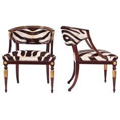 Pair of Gustavian Neo-Classical Tub Chairs  Sweden  circa 1820s  Horseshoe-shaped newly upholstered in faux zebra, back joined to rectangular seat, down swept supports with golden ormolu head mounted over garrya husk-carved apron, raised on circular section foliate carved and fluted front legs, headed by blocked rosettes, with rear saber legs. Light walnut and original gilt finish. Priced per pair.