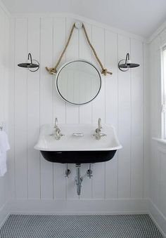 Black and white cottage bathroom features walls clad in vertical shiplap lined with a rope hung mirror illuminated by black and white vintage barn wall sconces over a black and white trough sink, Kohler Brockway Sink, alongside a white penny tiled floor accented with black grout.