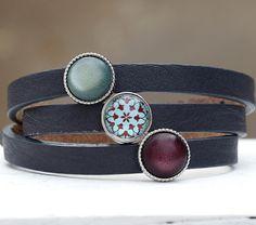 3- fach gewickeltes Armband aus weichen italienischen Leder mit 3 Metallschiebeperle. In die Metallschiebeperlen wurde zwei matt-farbige Polariscabochons und ein handgefertigter Glascabochon mit...