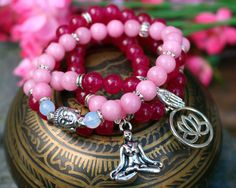 You get exactly whats in the picture, all my jewelry is one of a kind. - FOUR BRACELET STACK - you are purchasing FOUR bracelets that come together! - Deep, classy Brazilian ruby (rose red tourmaline) round beads - Bold rose quartz round beads - Silver tone spacer beads -Four unique silver tone charms (lotus palm, lotus flower, yoga pose, Buddha head) - 7 Inches un-stretched (approximately). These bracelets best fit people with a small/medium frame. - Ships from Canada.  This bracelet stack…