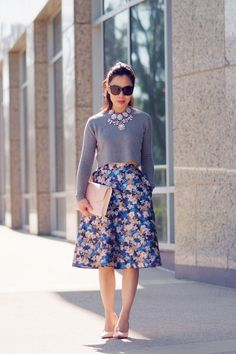 Saia rodada florida, blusa curta, colar e acessórios doces.