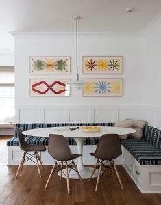 transitional dining room by indi interiors white wood built in corner banquette off of kitchen - saarinen table eames chairs pendant custom upholstery and storage geometric art