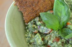 Raw cracker with avocado, basilpesto oil and cherry tomatoes
