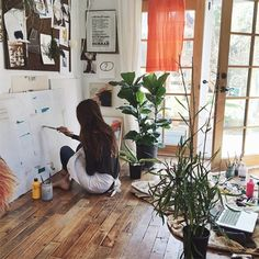 love the white walls, wood floors, green plants, and the pop of airy orange