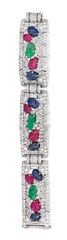 PLATINUM, CARVED COLORED STONE AND DIAMOND BRACELET, MARCUS & CO.  The openwork bracelet of foliate design, set with baguette, square, round, old European and single-cut diamonds weighing approximately 19.00 carats, decorated with carved ruby, sapphire and emerald leaves, length 6 5/8 inches, signed Marcus & Co., one diamond missing; circa 1930.