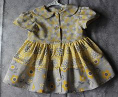 Hand made, cotton, infant dress in shades of yellow, white and grey. One available in each size 3-6months, 6-12 months, 12-18 months and 18-24 months. Made in Yukon, Canada by Suzanne Flumerfelt.