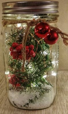 This is a Christmas decor piece that is made from a mason jar. The jar is filled with Christmas greenery, snow, and LED lights. These jars make beautiful centerpieces for the holiday, or even a wedding centerpiece for a Christmas wedding. Christmas Greenery, Christmas Jars, Christmas Table Decorations, Christmas Holidays, Christmas Wedding Centerpieces, House Decorations, Homemade Christmas, Beautiful Christmas Decorations, Christmas Island