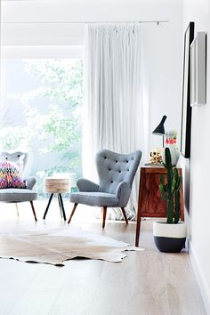 I like the composition of furniture and cow hide rug in this set up from Fenton and Fenton